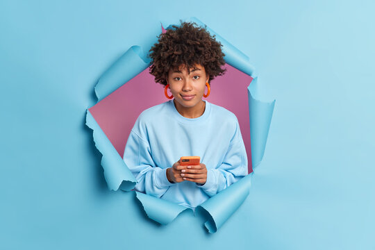 Pretty curly haired woman uses mobile phone for texting in social networks holds mobile phone waits for new message wears sweatshirt breaks through paper background. Modern technologies concept