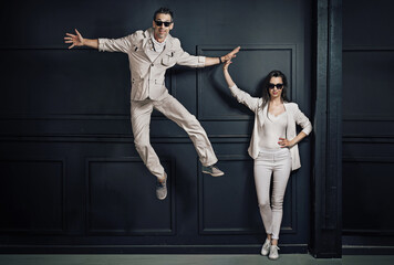 Attractive couple posing on the black wall background