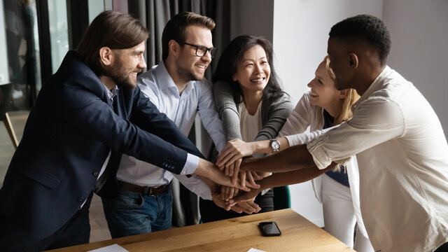 Excited happy young and mature mixed race colleagues joining hands, strengthening team spirit, motivating each other at meeting. Laughing diverse multiracial business people celebrating shared success