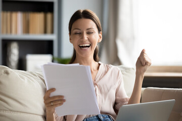 Fototapeta Overjoyed woman reading good news in letter, celebrating success, showing yes gesture, sitting on couch with laptop on laps, happy young female received money refund, job promotion, loan approve