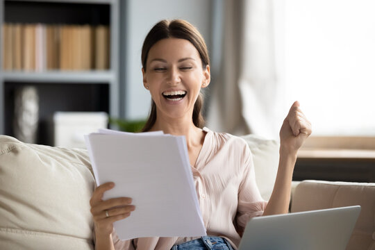 Overjoyed woman reading good news in letter, celebrating success, showing yes gesture, sitting on couch with laptop on laps, happy young female received money refund, job promotion, loan approve