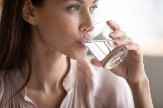 Close up attractive woman drinking pure fresh mineral water, preventing dehydration, young female holding glass, healthy lifestyle and good daily habit concept, natural beauty, skin and health care