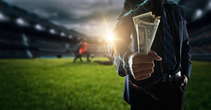 Concept of betting bet sport.businessman holding large amount of bills at Soccer stadium in background.