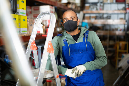 Warehouse worker in protective mask stands next to stepladder and tool shelves in a hardware store