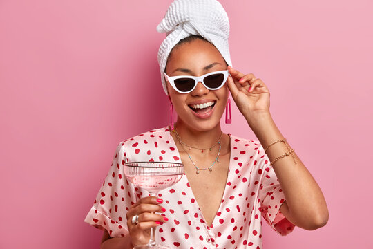 Positive African American woman laughs happily wears sunglasses bath towel dressing gown holds glass of martini cocktail has fun on domestic party smiles broadly isolated over pink background