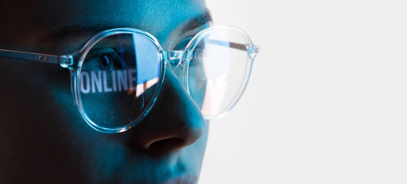Close up view of blue eye in glasses with futuristic holographic interface to display data. Portrait of beautiful young woman, half of face. Augmented reality, future technology, internet concept.