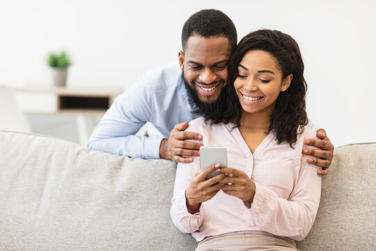 African american couple sitting on couch, using cellphone