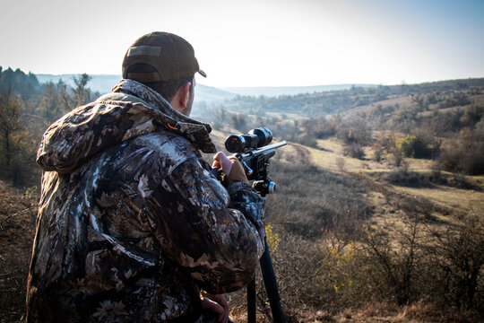 hunter sits in ambush and waits for game, rifle on tripod, perspective visible, soft focus