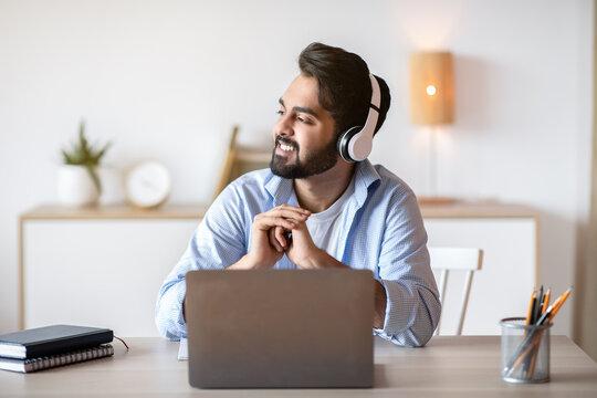Smiling arab man in headphones listening music while working on laptop