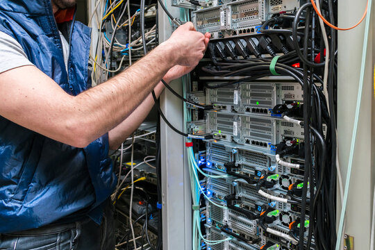 There is a close-up of the switching of Internet communication wires. Technical work in the data center server room. Maintenance of computer equipment on the hosting site