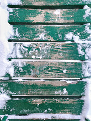 Snow on a wooden plank floor of an open terrace close-up. Green wooden snowy background.