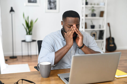 Desperate young African-American business entrepreneur in smart casual attire, touching the face, feeling stressed and overwhelmed while sitting in the office with an open laptop and a cup of coffee