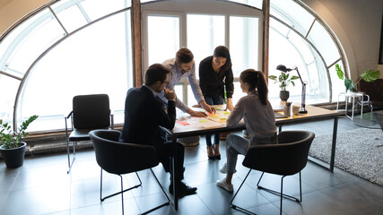 Diverse employees working with project documents, using sticky papers, writing notes, colleagues developing business project strategy, marketing plan, analyzing charts and diagrams in modern office - fototapety na wymiar