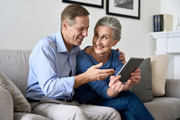 Happy older mature couple using digital tablet sitting on sofa at home. Smiling senior retired...
