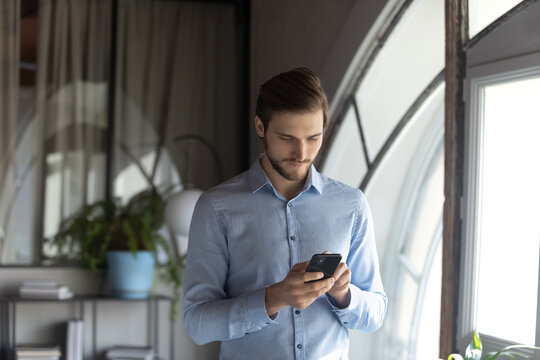 Close up confident businessman using phone, standing in office, focused serious entrepreneur executive looking at phone screen, reading or writing business email, browsing apps, searching information