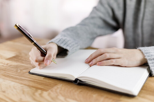A young girl writes in a notebook on a wooden table.