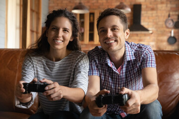 Overjoyed millennial couple relax at home together have fun playing computer video games. Excited...