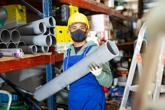 Latin american foreman wearing protective mask looking for PVC pipes and fittings for plumbing works in building hypermarket. Working and shopping concept in pandemic