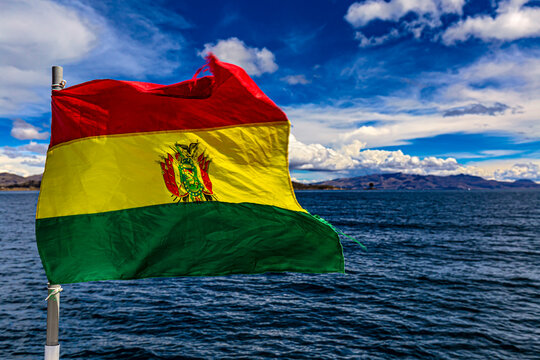 The national flag of Bolivia fluttering in the wind against Lake Titicaca background. Selective focus in the flag