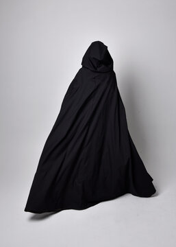 Full length portrait of pretty black haired woman wearing long dark gown nada cloak.  Standing pose facing away from the camera, against a  studio background.