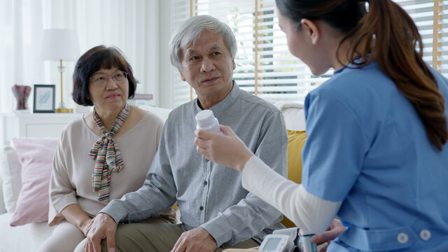 Young caregiver in scrubs uniform showing medicine bottle to elderly asian couple man and woman in home visit care nursing service.  Asian senior with assisted living medication monitoring concept.