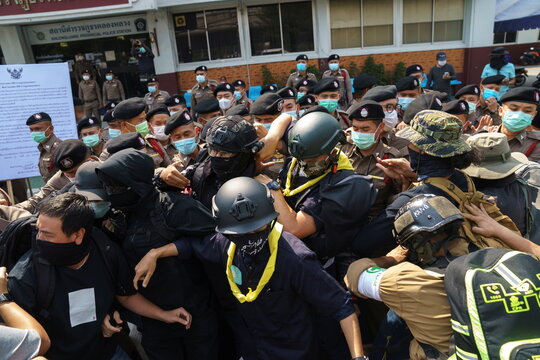 Volunteer guards of the anti-government protest movement scuffle with police officers at the Khlong Luang police station in Pathum Thani province