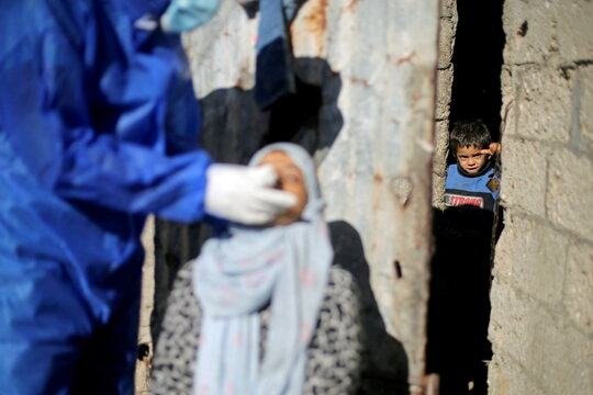 Medical workers test Palestinians for COVID-19 in Gaza