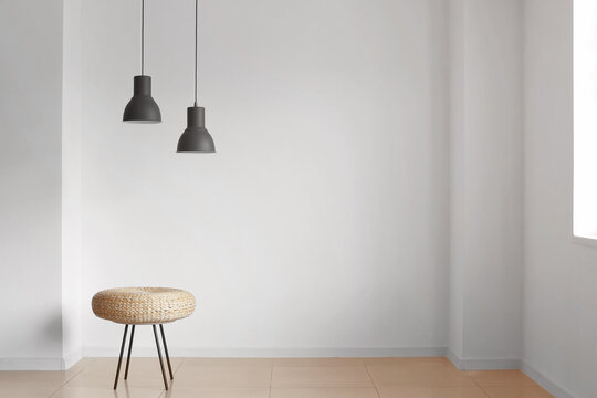 Pouf and lamps near light wall in room