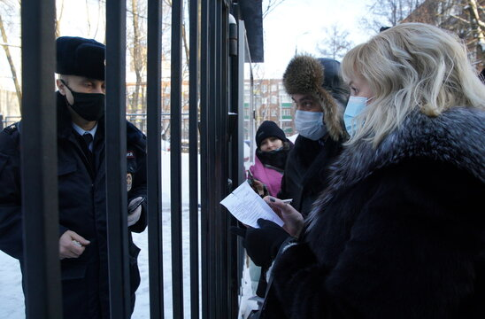 Olga Mikhailova and Vadim Kobzev, lawyers of Russian opposition leader Alexei Navalny, talk to a police officer outside a police station, in Khimki