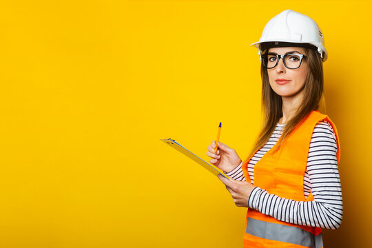 Young woman in a vest and hard hat holds a clipboard on a yellow background. Construction concept, new building. Banner