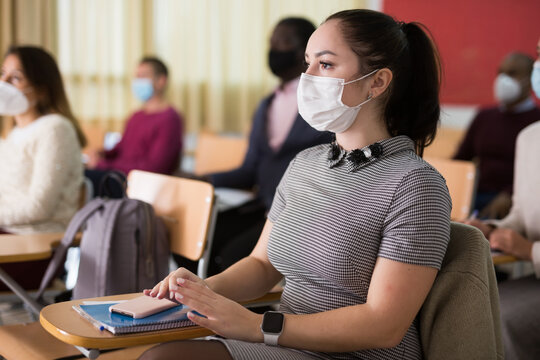 Group of students in protective mask listening attentively to teacher explaining material in classroom