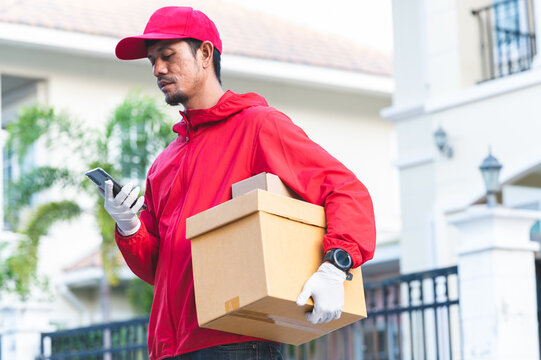delivery man in red uniform Look at the phone to find the customer address through the application.