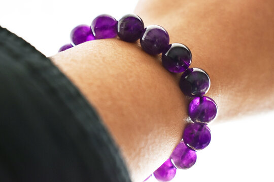 Amethyst bracelet on the wrist. Spiritual and healing crystal gemstone.