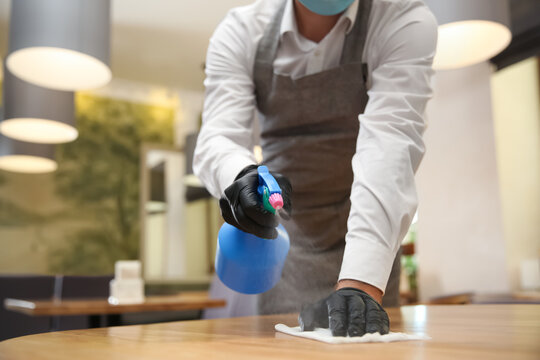 Waiter cleaning table with rag and detergent in restaurant, closeup. Surface treatment during coronavirus pandemic