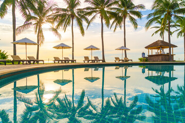 Beautiful luxury umbrella and chair around outdoor swimming pool in hotel and resort with coconut palm tree on sunset  or sunrise sky