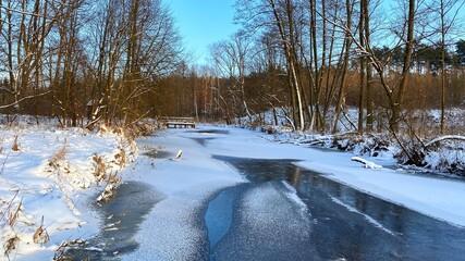 Fototapeta zimowy krajobraz częściowo zamarzniętej rzeki koło Włodawy dużo śniegu niebieskie niebo złota godzina  obraz