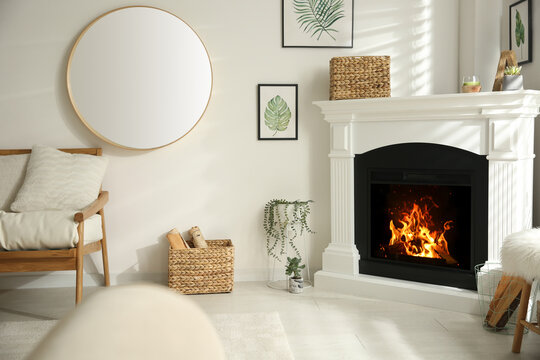 Bright living room interior with artificial fireplace and firewood in basket