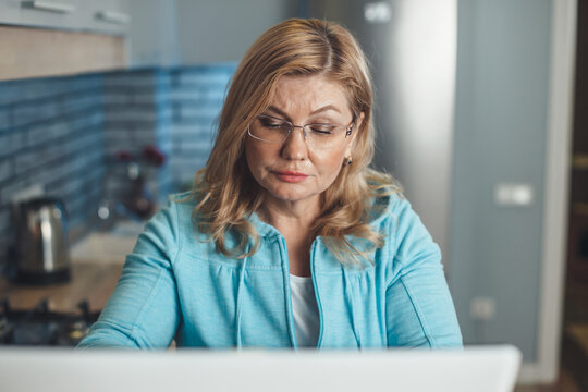 Senior blonde woman is concentrated working at home at the laptop remotely wearing glasses in the kitchen