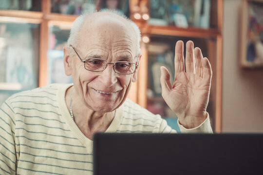 Old gray haired man in glasses hand up and calling to family by laptop.
