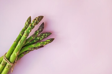 Bunch of fresh asparagus on pink background