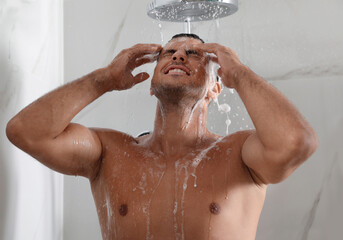 Handsome man washing hair in shower at home