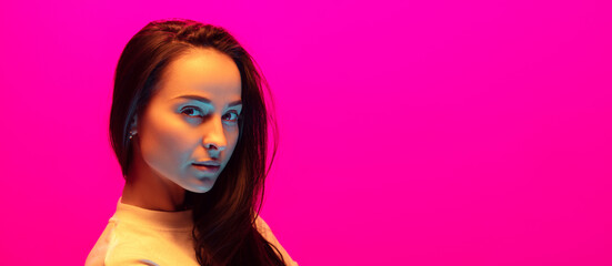 Serious. Caucasian woman's portrait isolated on pink studio background in mixed neon light. Beautiful female model. Concept of human emotions, facial expression, sales, ad, fashion. Flyer, copyspace. Fotomurales