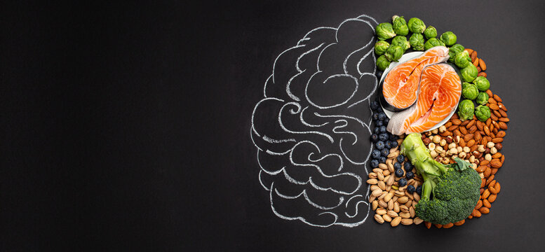 Chalk hand drawn brain picture with assorted food, food for brain health and good memory: fresh salmon, vegetables, nuts, berries on black background. Foods to boost brain power, top view, copy space