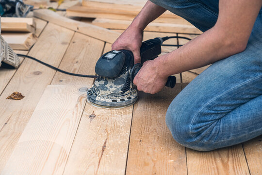 close up of a worker sanding wood planks with a grinder