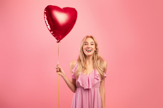 Portrait of joyful blonde woman in dress holding red heart shaped balloon for Valentine's Day on pink studio background