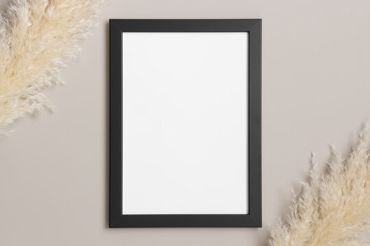 Top view of a black frame mockup with pampas decoration.