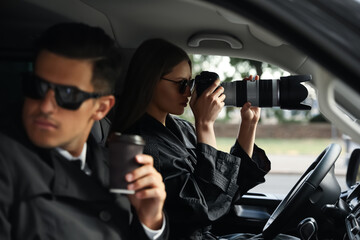 Private detectives with modern camera spying from car - fototapety na wymiar