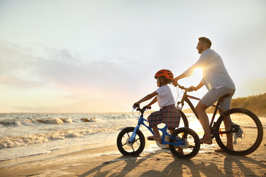 Happy father with son riding bicycles on sandy beach near sea at sunset
