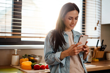 Smiling attractive young woman texting on mobile phone