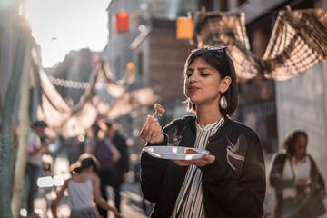 Obraz Beautiful young female tourist in city of Paris France enjoying holidays in beautiful little street festival eating street food - fototapety do salonu